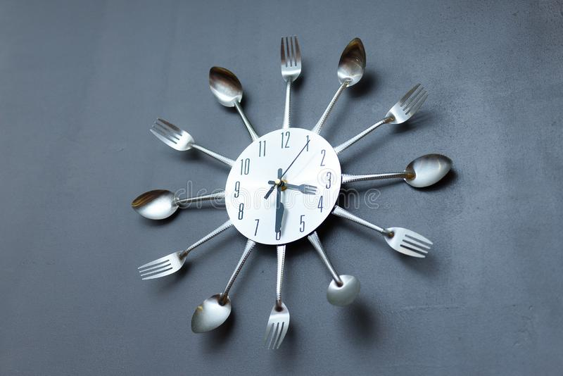 Clock in the kitchen, cutlery. Gray royalty free stock photo