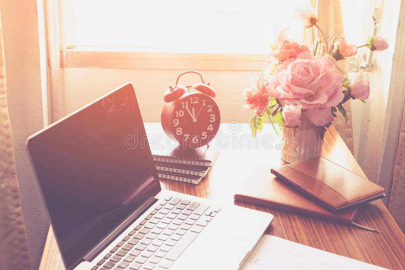 The clock, laptops, books on the table. stock photography