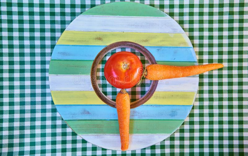 Clock made with a tomato and two carrots located on a table with green checkered tablecloth. Autumnal still life. Rustic Design royalty free stock photos