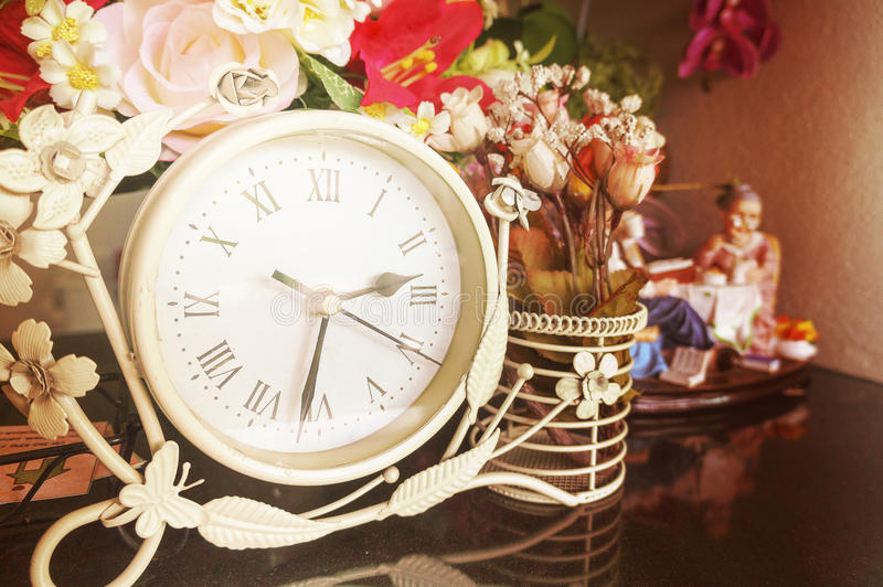 Clock making light soft vintage style. Clock located in front of the flower pot. making light soft and blur, vintage style stock photography
