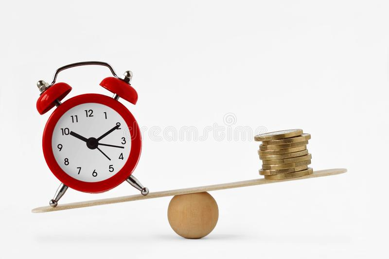 Clock and money on scales - Importance of time, time and money concept stock image
