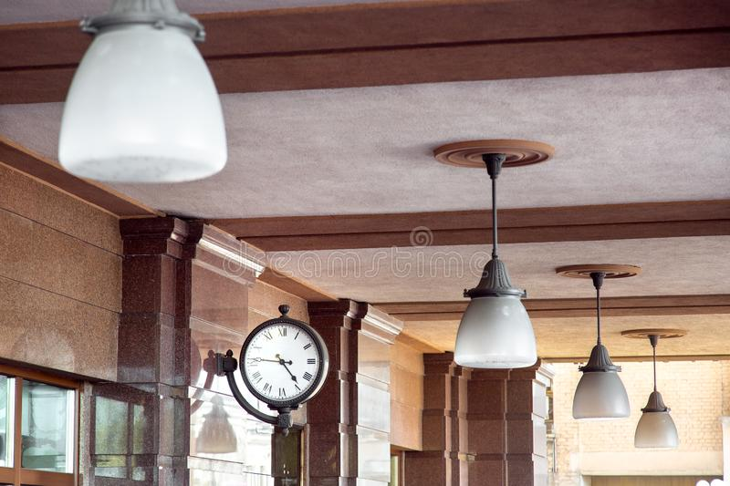 The clock is mounted on a brown marble wall. The clock is mounted on a brown marble wall and the ceiling lights are lamps with white shades stock images