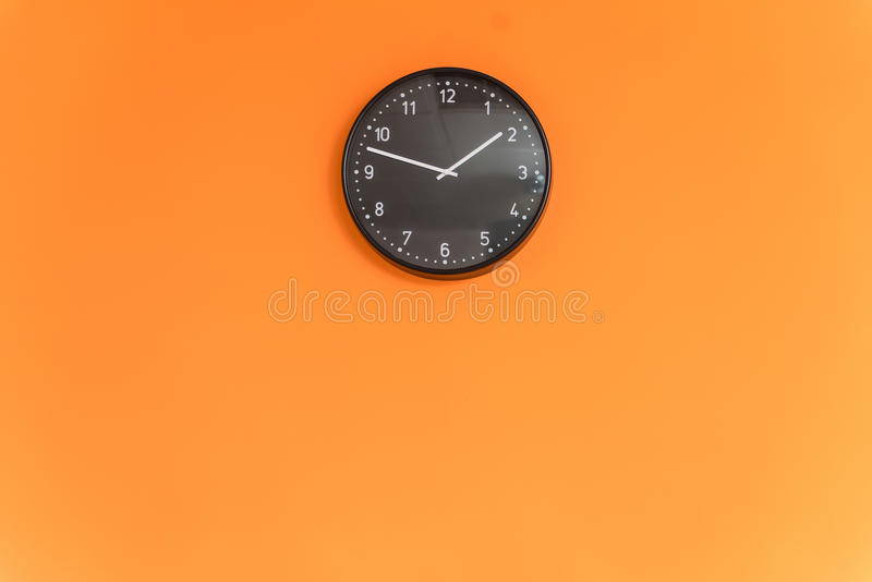 Clock on orange wall stock photography