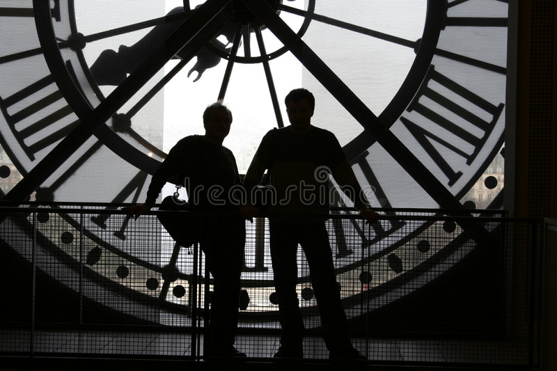 Clock at the Orsay Museum. 2 silhouettes against the clock at the Orsay Museum (Mus饠d'Orsay