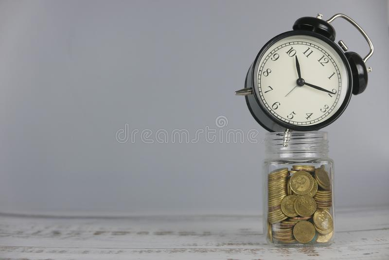 Clock over jar of gold coins. Money and time concept. Copy space for text or logo royalty free stock image