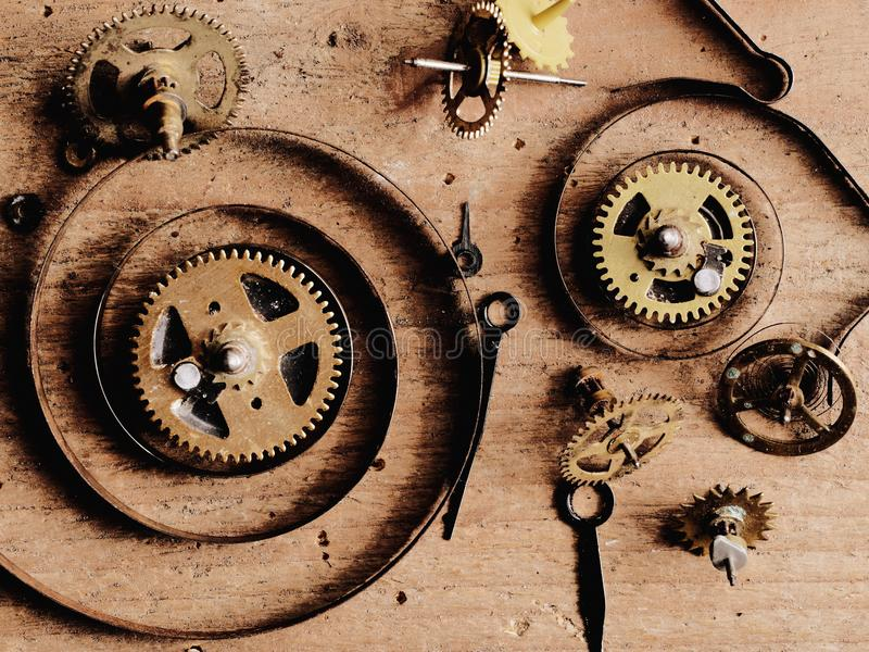 Clock parts wood. Various clock parts laid on a rustic wood background, viewed from above stock photography