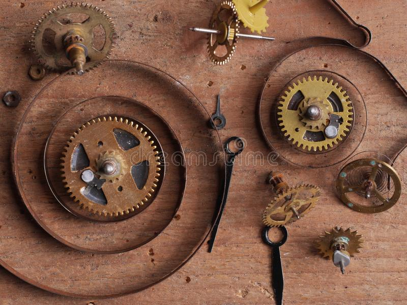 Clock parts wood. Various clock parts laid on a rustic wood background, viewed from above stock image