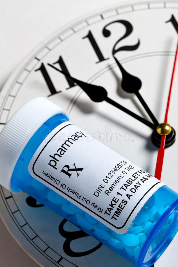 Clock and Pill Bottle. Concept for Healthcare And Medicine stock photos