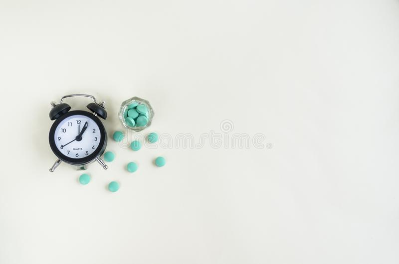 Clock and pills come out from a medicine bottle. pill time. copy space. stock image