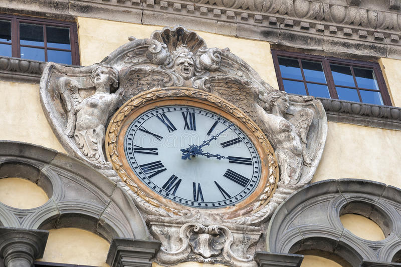 Clock on a public building of Lucca, Italy royalty free stock image