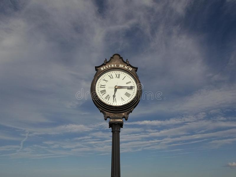 Clock, Revere Beach, Revere, Massachusetts, USA. Tall iron clock surrounded by cloudy blue sky at Revere Beach in Revere, Massachusetts, USA stock photography