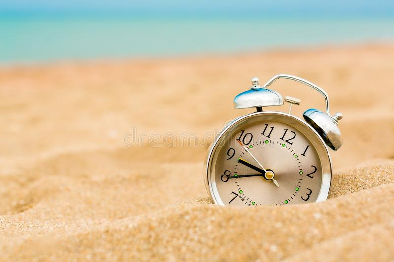 Alarm clock in sand on beach royalty free stock photos