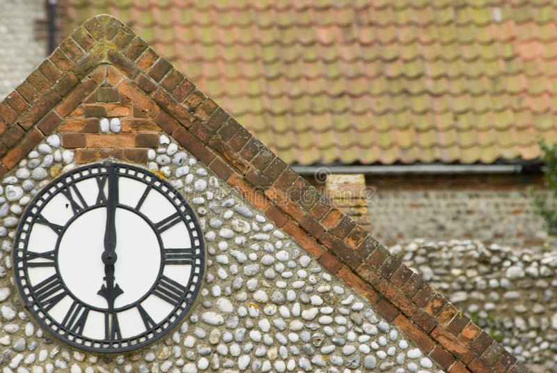 Clock at six o'clock. Roman numerals on outdoor wall clock on building with flint facing royalty free stock images