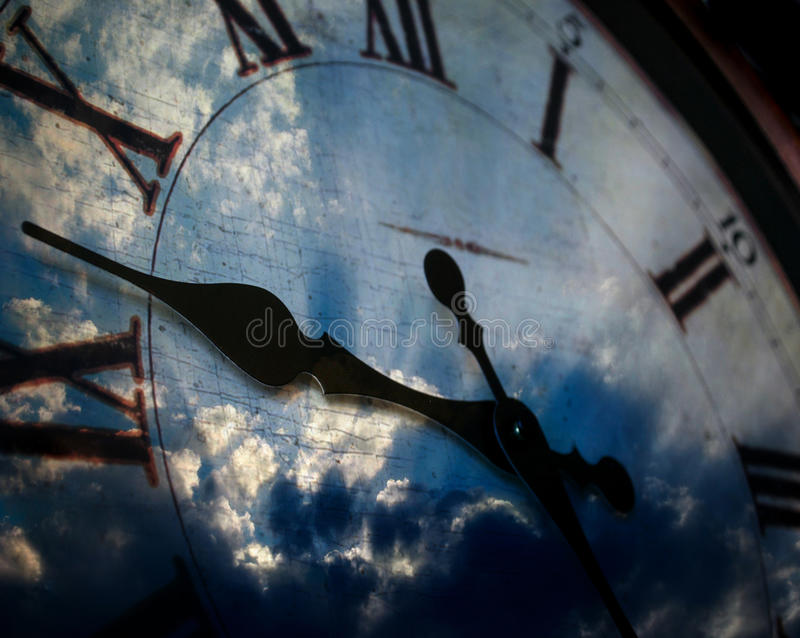 Clock and Sky. Detail of clock face with numbers and hands showing time and sky in background