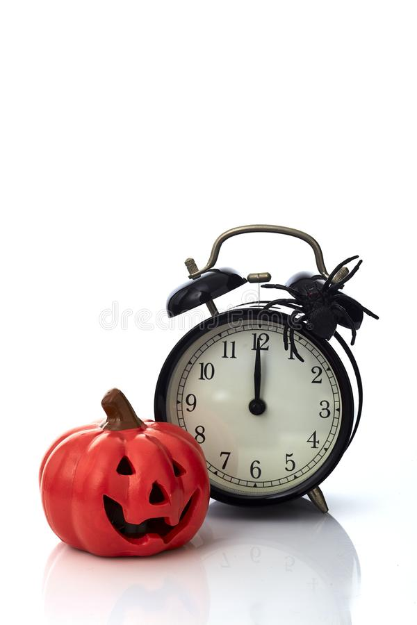 Clock with spider for Halloween celebration. Vintage Clock with spider and pumpkin for Halloween celebration on white background, minimal copy space for text royalty free stock photo