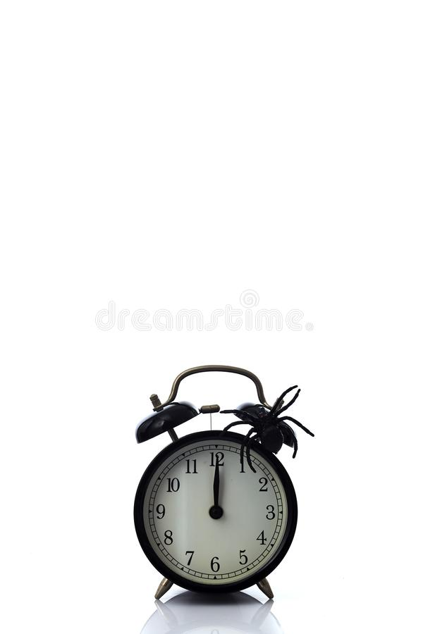 Clock with spider for Halloween celebration. Vintage Clock with spider for Halloween celebration on white background, minimal copy space for text royalty free stock photo