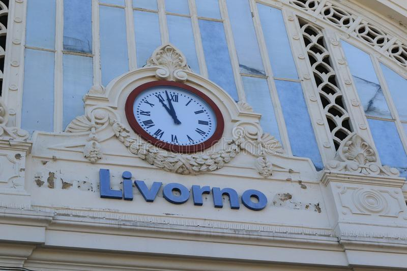 The clock at the station. Livorno Station Clock, on the facade as you enter the station stock photos