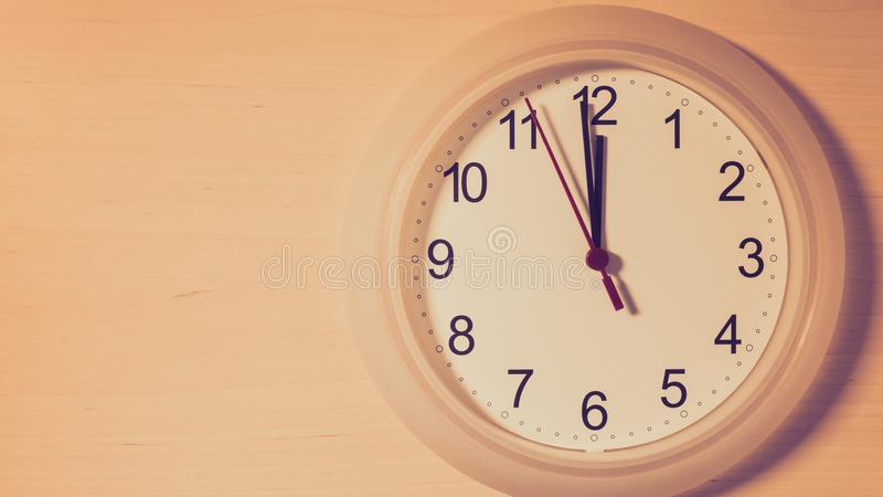 Clock ticking showing twelve hours. Clock hanging on wall ticking showing twelve hours royalty free stock photos
