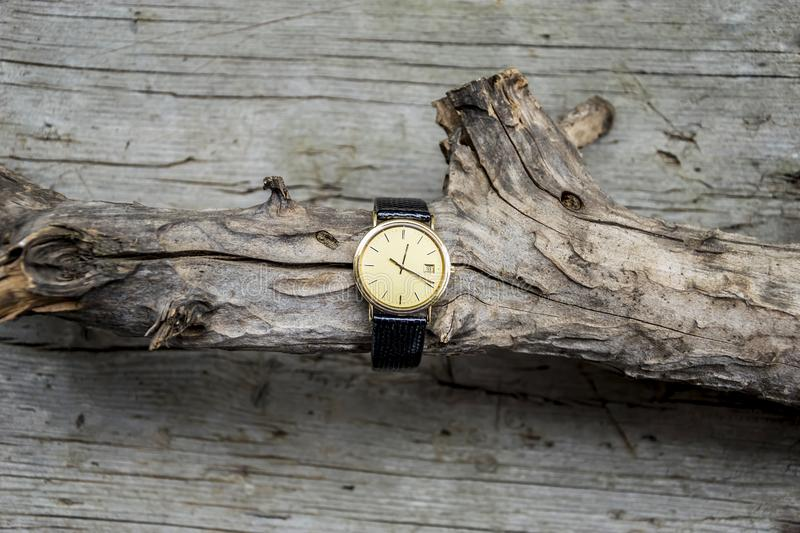 Gold wrist watch with leather strap on wooden background. Clock, time, watch, old, antique, , hour, white, vintage, minute, retro, pocket, alarm, gold, business royalty free stock photo