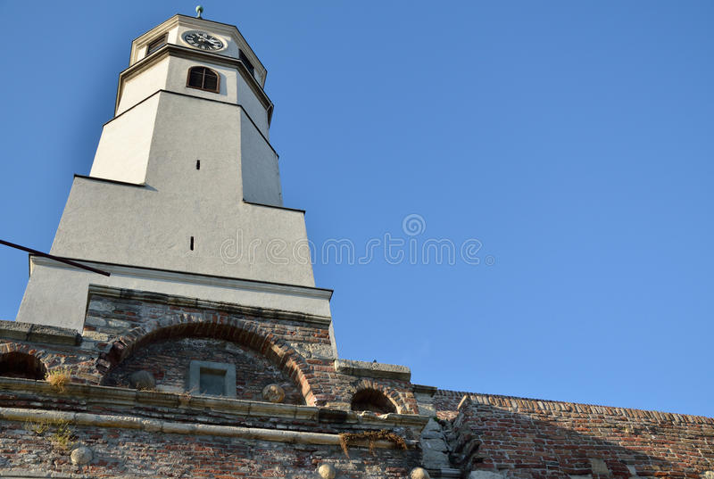 Clock tower on brick walls with blue sky royalty free stock image