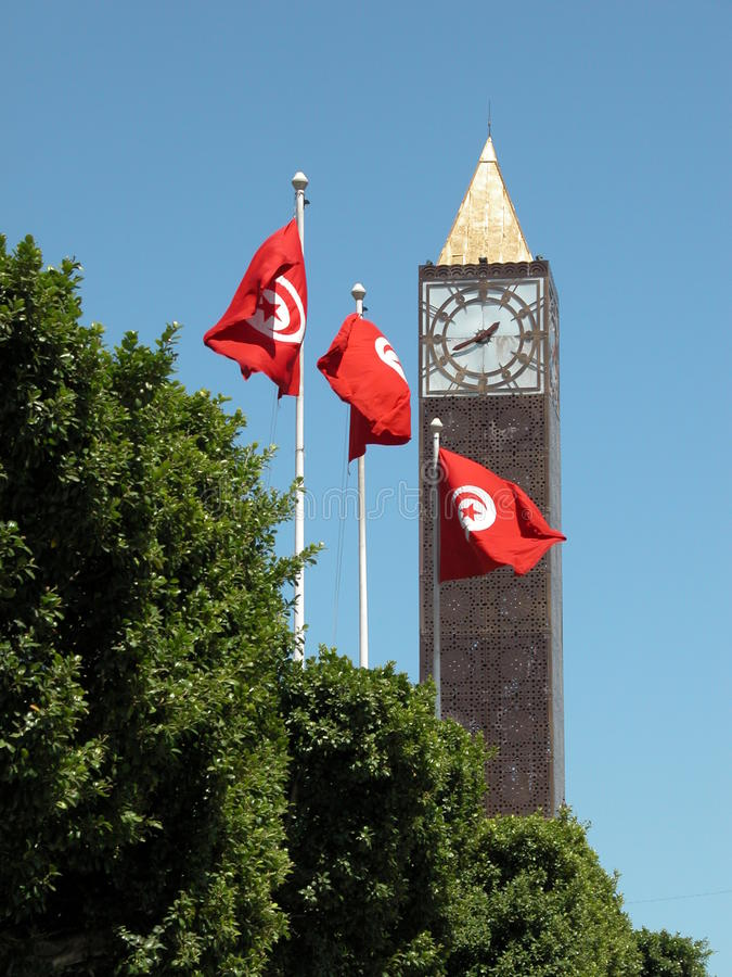 Clock tower and flags. Clock tower in Tunis city with flags in front stock photos