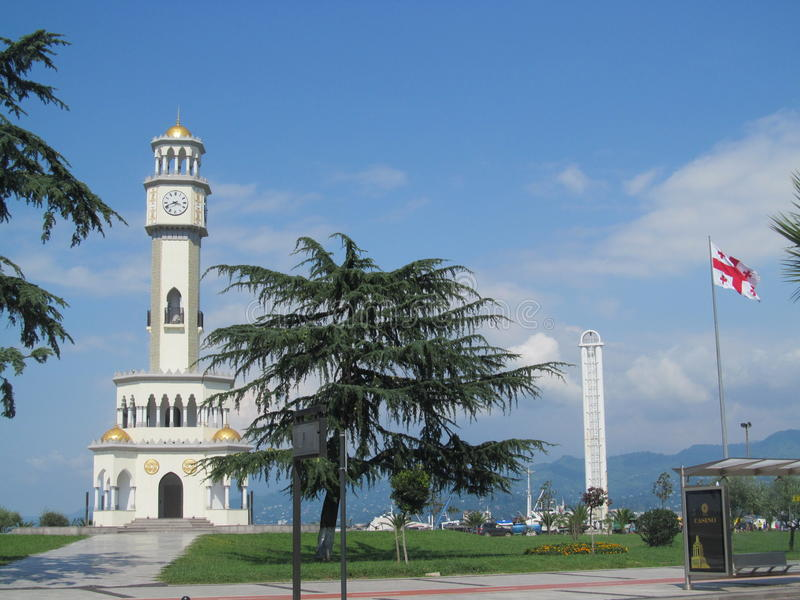 Clock tower and national flag of Georgia on the seafront in Batumi, Black Sea beach royalty free stock photos