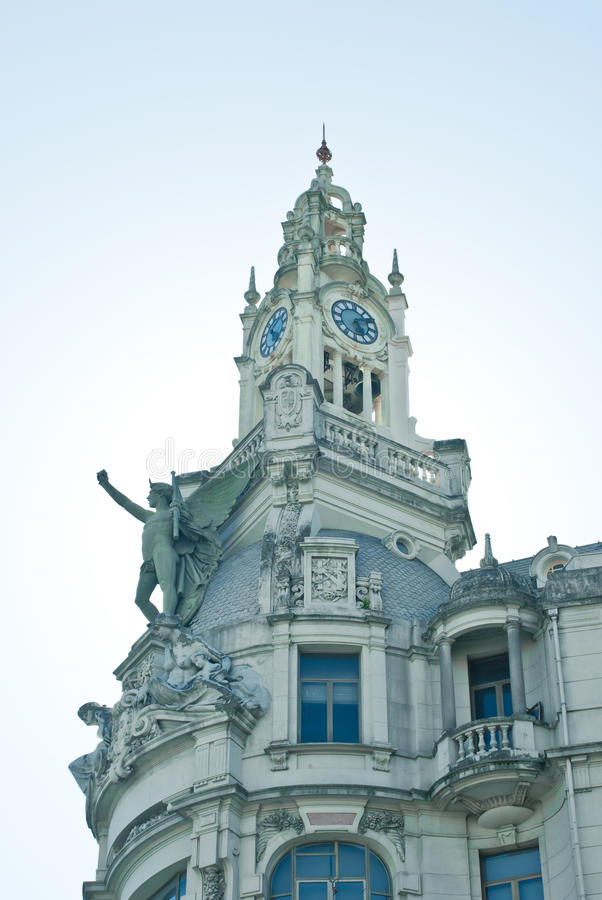 Clock Tower in Porto, Portugal. A clock tower with a statue up front from frog perspective, taken in Porto, Portugal royalty free stock photo