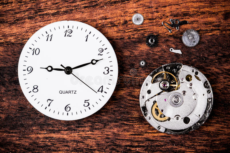 Clock. Various clock parts (cogs, hands, springs) laid on a rustic/antique wood background, viewed from above royalty free stock image