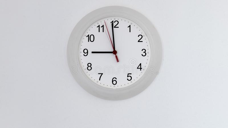 Clock on wall showing nine hours. Clock hanging on white wall showing nine hours stock photo