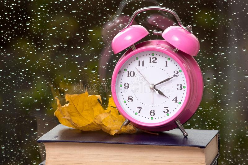 Clock and yellow maple leaf on a book against a window with drops of rain on the glass_ stock images