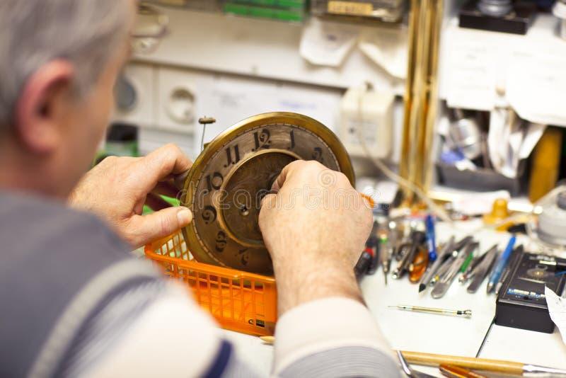 Clockmaker. In his workshop repairing stock photos