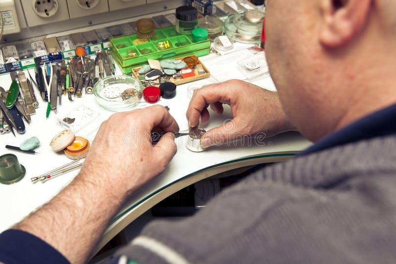 Clockmaker. In his workshop repairing stock images