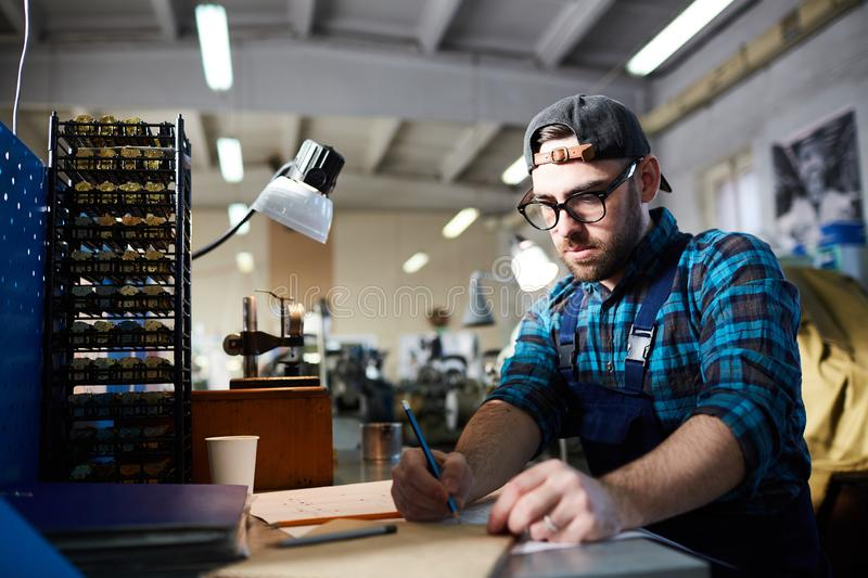 Clockmaker at Factory. Portrait of modern factory worker taking notes sitting at table in workshop, copy space royalty free stock image