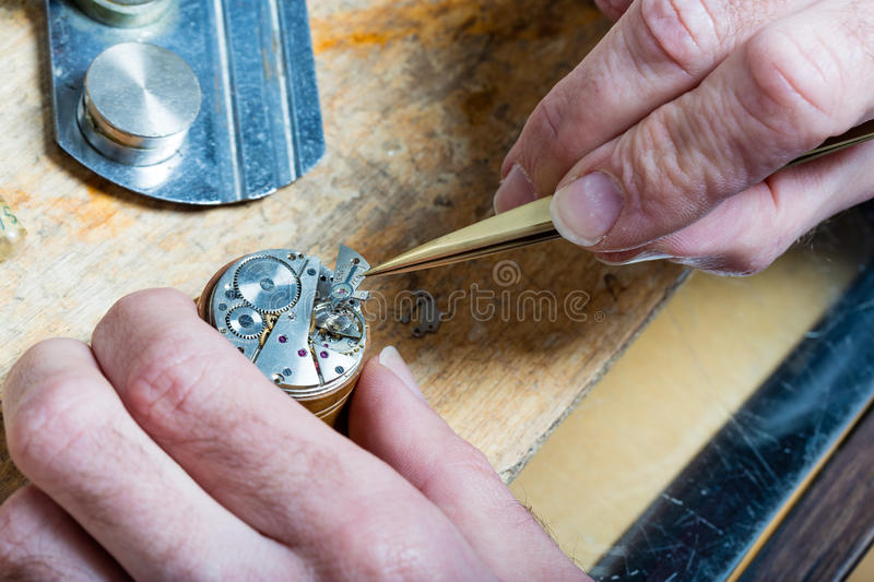 Clockmaker fixing an opened watch. Closeup of the hands of a watchmaker placing some clockworks with tweezers and fixing it royalty free stock images