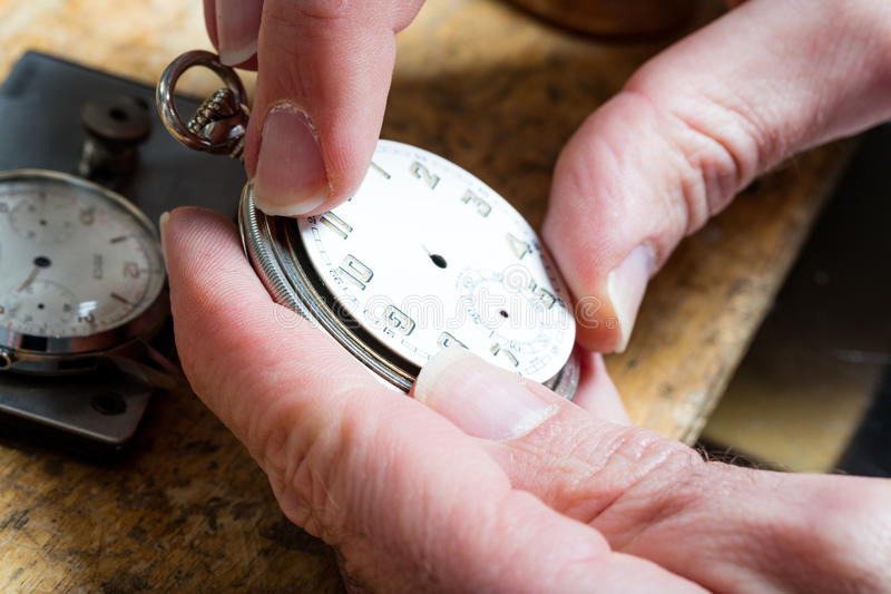 Clockmaker fixing a turnip pocket watch detail. Closeup of hands of a clockmaker placing the quadrant of a turnip pocket watch royalty free stock image