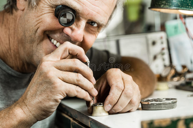 Clockmaker repairing wrist watch. And smiling to the camera royalty free stock photos