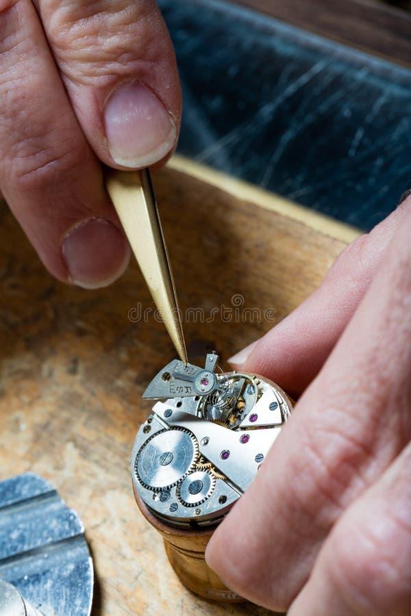 Clockmaker som fixar en öppnad klocka arkivbilder