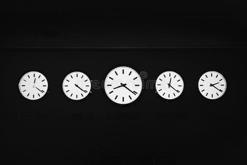 Five Clocks of Different Times. Clocks showing different timezones of different countries placed next to each other in a dark room stock image