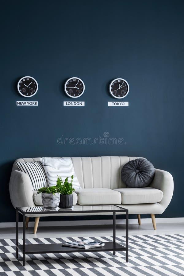 Time zones clocks above sofa royalty free stock photos