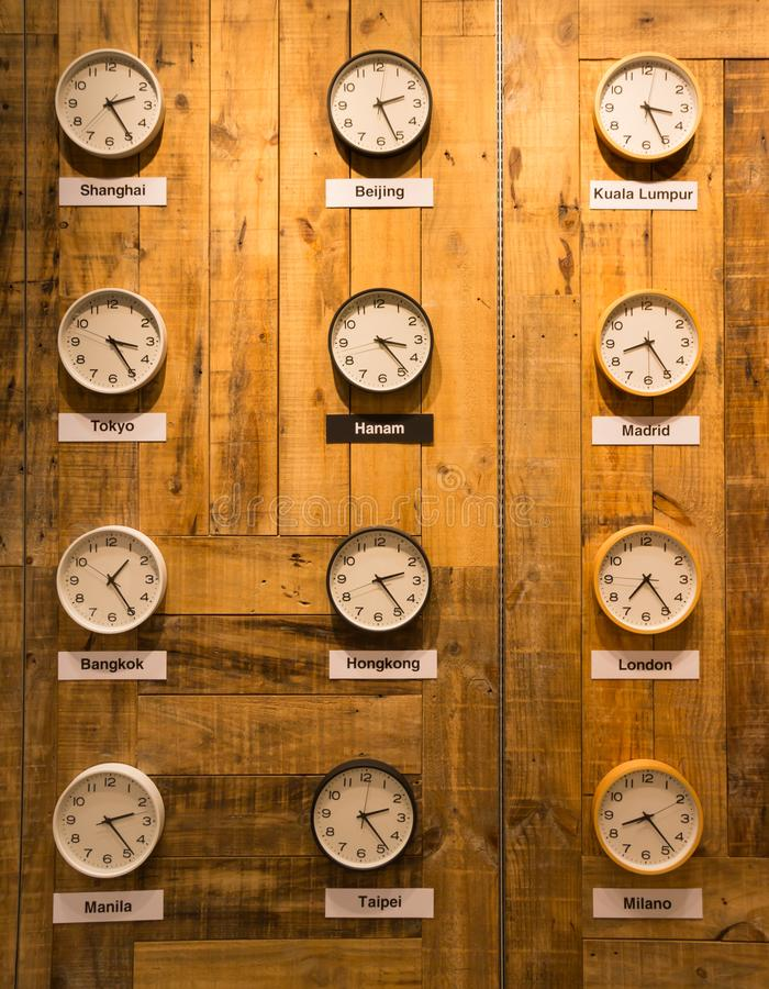 clocks on a wall with time zone of different cities stock photo