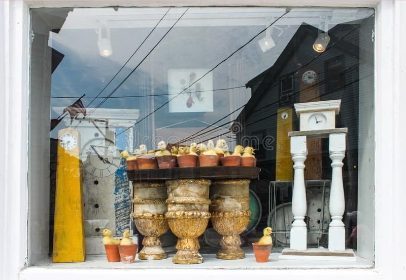 Clocks in a window - Reflections and display of antique clocks and baby ducks in flower pots in Cape Cod window with another clock royalty free stock photography