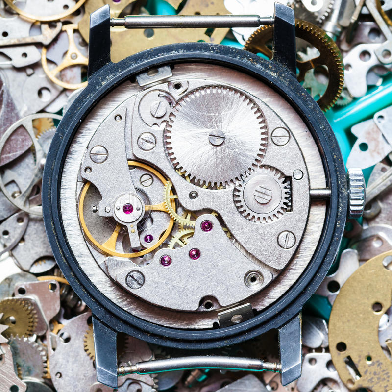 Clockwork on heap of clock spare parts. Watchmaker workshop - mechanical clockwork on heap of clock spare parts royalty free stock image