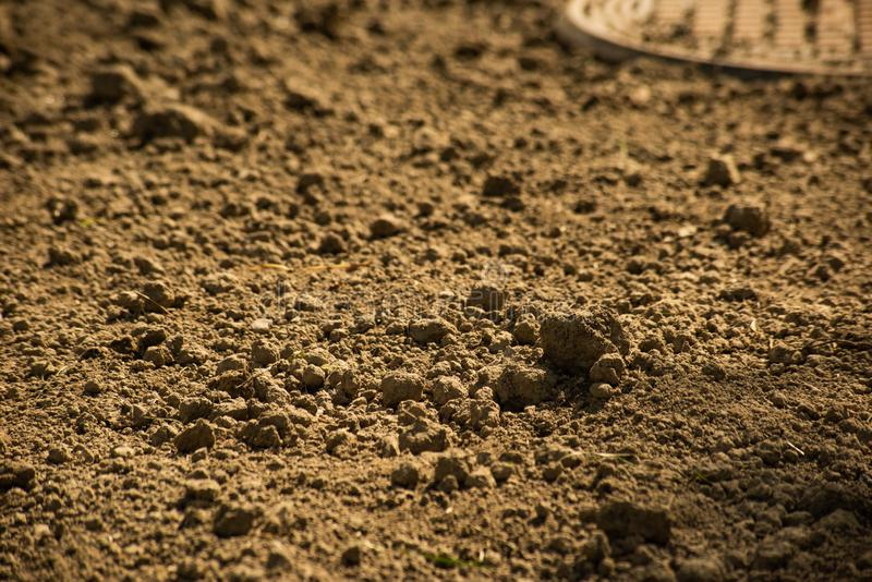 Clods of dry brown ground and manhole. Clods of dry brown ground and sewer hatch stock images