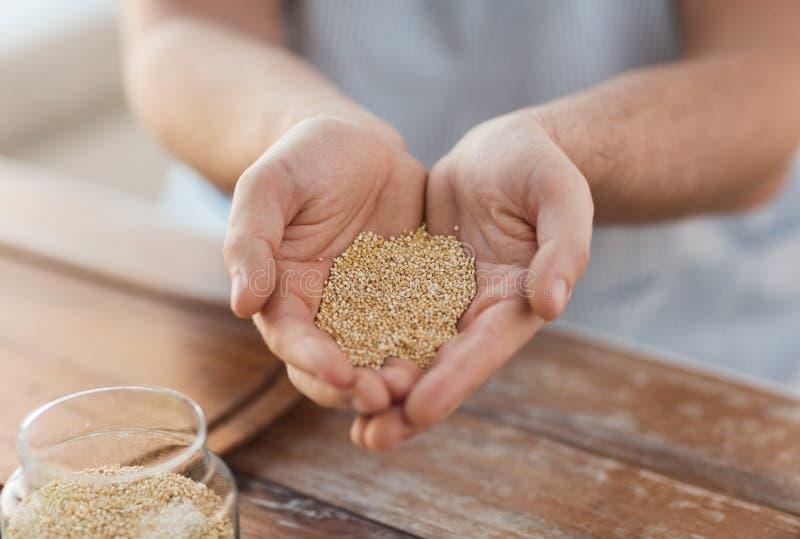 Cloes omhoog van mannetje tot een kom gevormde handen met quinoa royalty-vrije stock fotografie