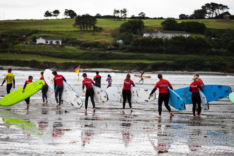 Clonakilty Irland - studenter från en lokal surfa skola att ta deras bräden in i vattnet på den Inchydoney stranden royaltyfri fotografi
