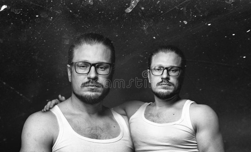 Cloning people concept. Creative male portrait. Black and white image with scratches stock photo