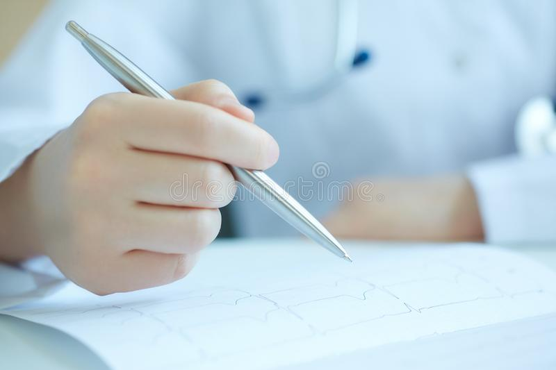 Closу up of female doctor hand with pen examining patient cardiogram chart. Female doctor examining patient cardiogram chart. Professional conversation royalty free stock image