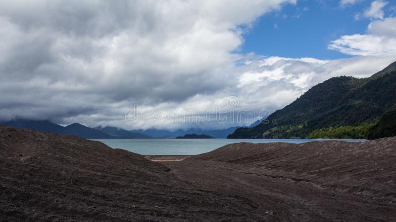 Clos to the lake. Hiking adventure on Osorno Volcano in Los Lagos Region of Chile. .Windy and rainy weather makes stock photo