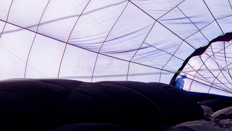 Clos-up del interior de un globo azul del aire caliente con la silueta de un hombre foto de archivo
