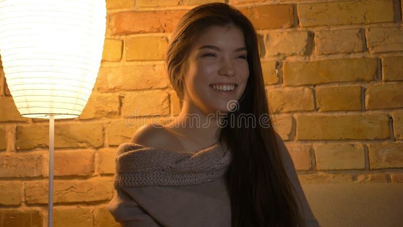 Closdeupspruit van jong leuk Kaukasisch wijfje die op een komedie op TV letten en cheerfully bij comfortabel huis binnen glimlach stock foto's